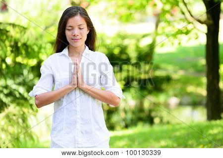 Young woman with hands clasped meditating in park. She is in casuals. Attractive female with eyes closed practicing yoga in nature.
