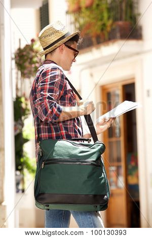 Young Travel Man Holding Bag And Reading Map