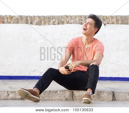 Guy Laughing And Sitting Outside On Sidewalk With Cell Phone