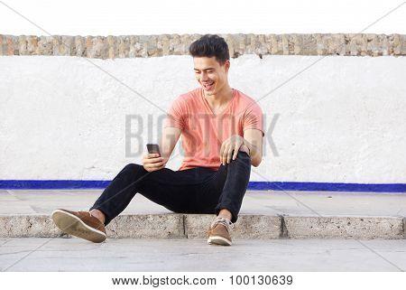 Cool Guy Sitting On Sidewalk Looking At Mobile Phone