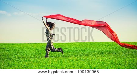 Beautiful young woman jumping on a green meadow with colored tissue