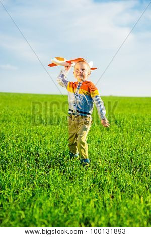 Happy boy playing with toy airplane against blue summer sky and green field background.