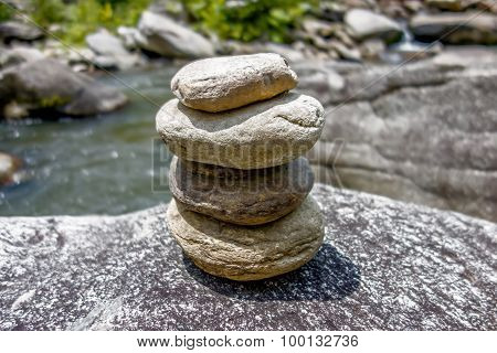 Stack Of Round Smooth Stones Near Mountain River