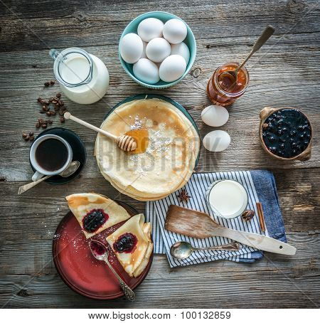 prepared pancakes and coffee among ingredients on wooden background