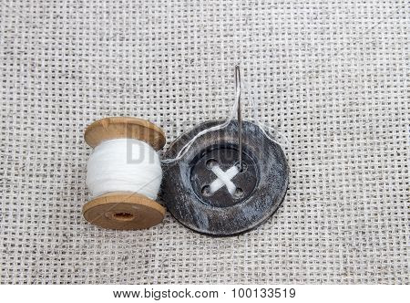 wood spool with white thread, needle and sewn stitch large wood sewing button scrapbooking