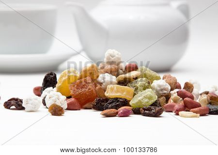nuts and dried fruits, on a background of a teapot, Cup closeup