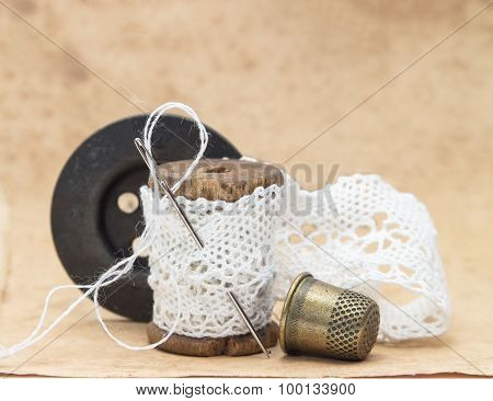 white lace ribbon, wound on a wooden bobbin with needle for sewing, a large black wooden button and