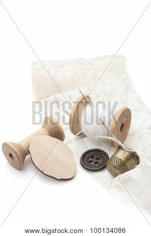 thread for sewing on wooden spools with needle, empty spool of thread, buttons, metal thimble, and a