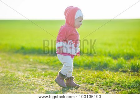 Happy little girl walking in the meadow and looking at sun