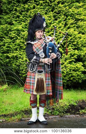 INVERARAY,  SCOTLAND - JULY 28 2015 : Scottish piper, in full national costume, plays the Bagpipes.