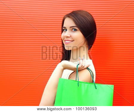 Portrait Of Beautiful Young Smiling Woman With Shopping Bag Over Bright Red Wall