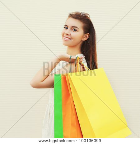Portrait Of Beautiful Young Smiling Woman With Shopping Bags Outdoors