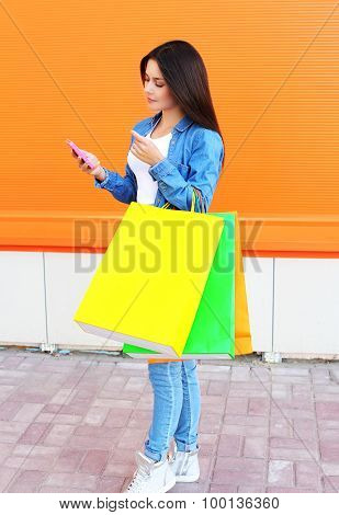 Beautiful Young Woman With Shopping Colorful Bags In Jeans Clothes Using The Smartphone Over Orange