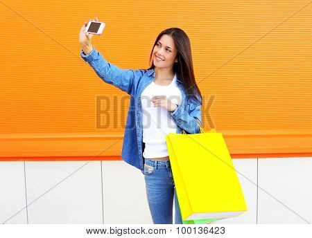 Happy Pretty Young Woman With Shopping Bags In Jeans Clothes Makes Photo Self-portrait On The Smartp