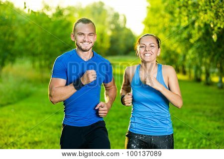 Runners training outdoors working out. City running couple jogging outside.