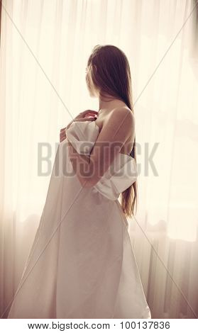 Beautiful lady with long hair wrapped in bedsheet by window