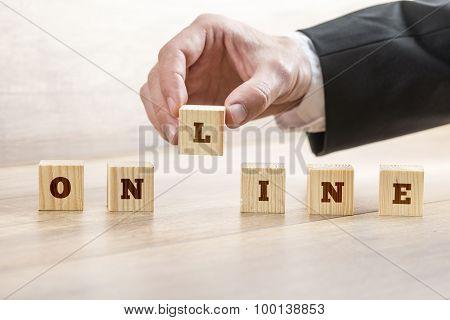 Closeup Of Businessman Hand Assembling Word Online With Six Wooden Cubes
