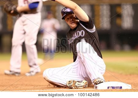 DENVER-AUG 21: Colorado Rockies catcher Nick Hundley slides into third base during a game against the New York Mets at Coors Field on August 21, 2015 in Denver, Colorado.