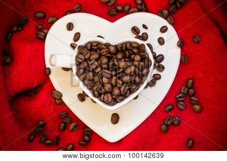 Heart Shaped Cup With Coffee Beans On Red