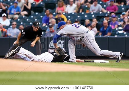 DENVER-AUG 21: New York Mets firstbaseman Lucas Duda tags out Colorado Rockies outfielder Charlie Blackmon during a game at Coors Field on August 21, 2015 in Denver, Colorado.