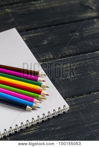 Colored Pencils And Notebook On A Dark Wooden Surface