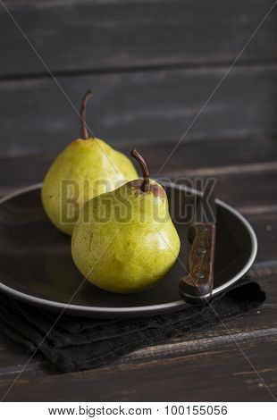Fresh Yellow Pears On A Brown Plate On A Dark Wooden Surface