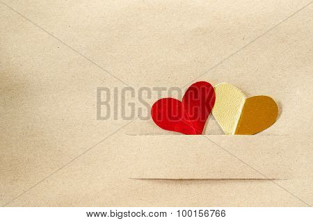 Gold Heart And Red Heart On Vintage Brown Paper.