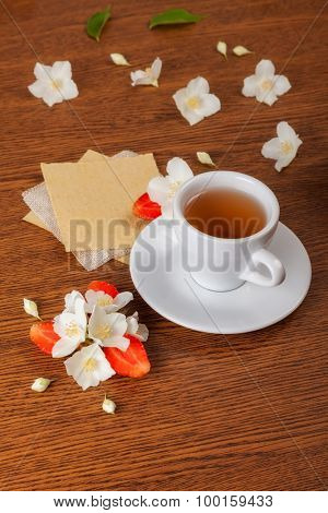 white cup of green tea. jasmine flowers with strawberry halves. texture blank for writing. still life