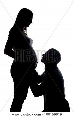 Silhouette of happy husband looking at pregnant wife
