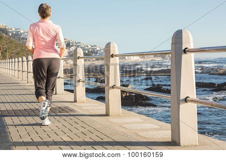 Rear view of sporty woman jogging at promenade on a sunny day