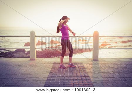 Tired fit woman checking smart watch at promenade on a sunny day