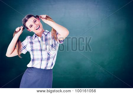 Geeky hipster holding her pigtails against green chalkboard