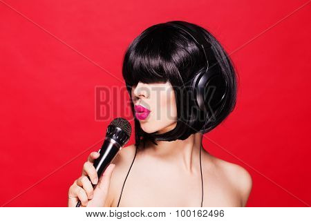 Stylish girl singing with a microphone, red background. Karaoke