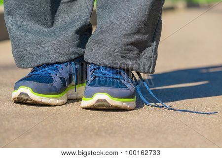 Men Feet In Sneakers With Untied Lace