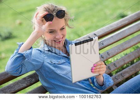 Lovely blond woman with electronic tablet in hands