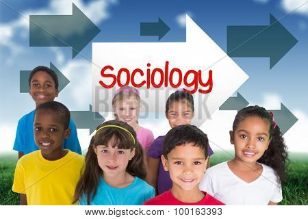 The word sociology and elementary pupils smiling against blue sky over green field