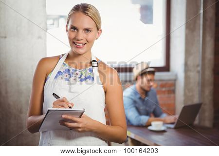 Portrait of smiling blonde waitress taking order in front of customer at coffee shop