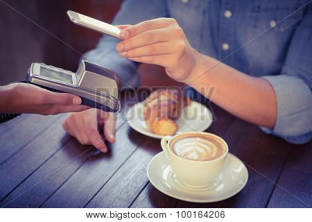 Male customer paying with smartphone at coffee shop