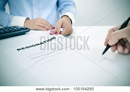 closeup of the hand of a man who is signing a resignation document on a desk in front of a young woman