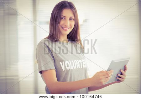 Portrait of smiling brunette volunteer with tablet in the office