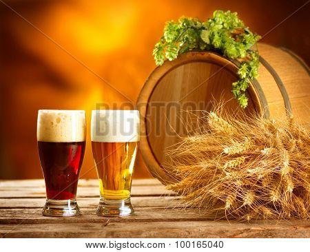 Beer. Still life with Vintage beer barrel and two glasses of dark and light beer. Fresh amber beer concept. Green hop and gold wheat on wooden table. Ingredients for brewery. Brewing traditions