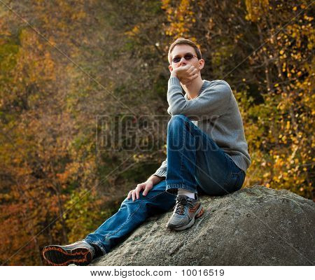 Young Hiker Relaxing On Rock