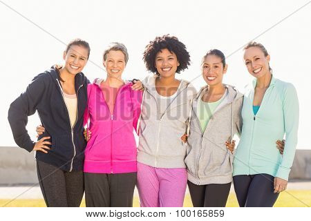 Portrait of smiling sporty women with arms around each other in parkland