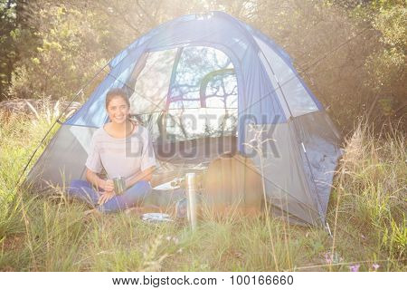 Portrait of smiling brunette camper sitting in tent in the nature