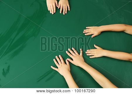 Children hands on blackboard background