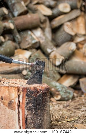 Hatchet in stump with firewood