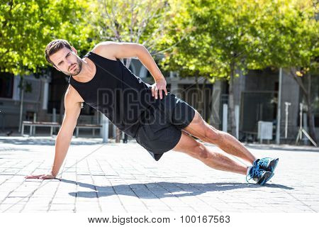 Portrait of an handsome athlete doing side plank on a sunny day