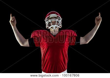 American football player triumphing against black background