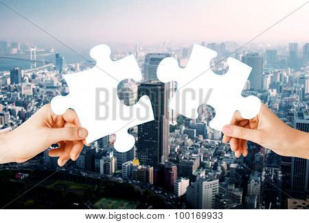 nature, ecology, energy saving, urbanization and people concept - close up of couple hands trying to connect puzzle pieces over city background