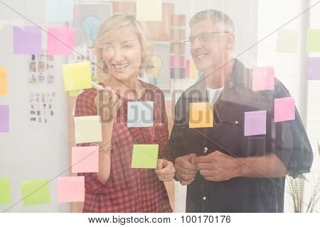 Smiling business team pointing post its on the wall at office